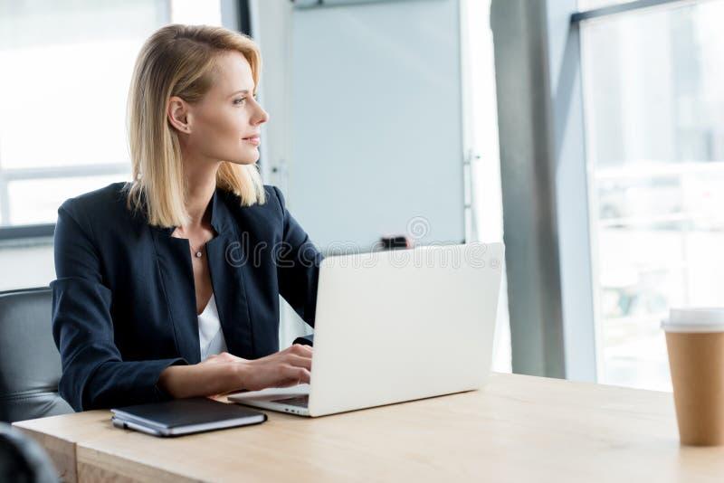 zadumany buisnesswoman patrzeje oddalony podczas gdy używać laptop obraz stock