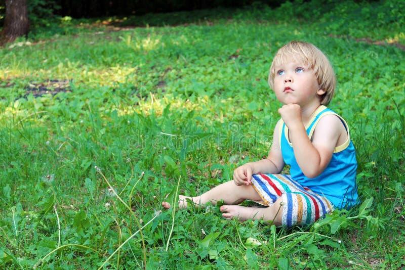 Zadumany chłopiec obsiadanie na zielonej trawie, marzycielka zdjęcie stock