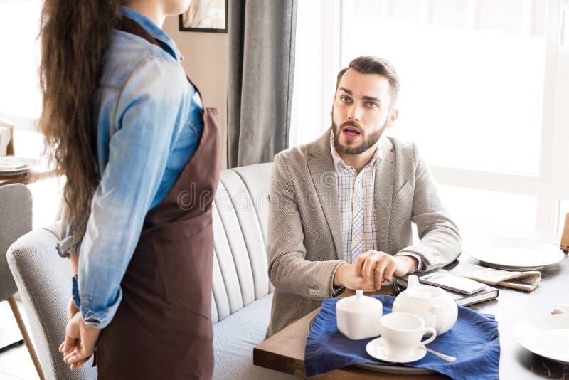 Zadumany klient pyta kelnerki w kawiarni zdjęcia royalty free