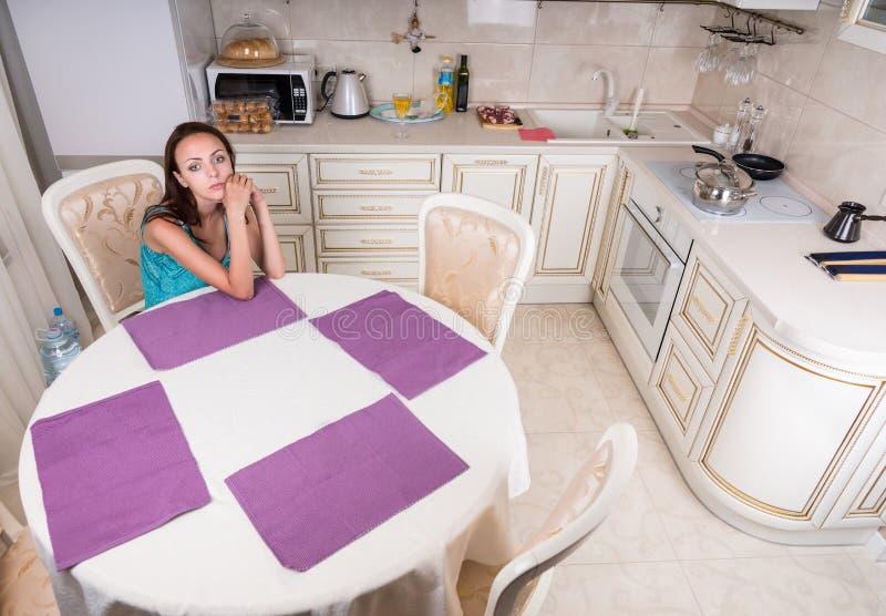 Zadumany kobiety obsiadanie przy stołem w kuchni obraz royalty free