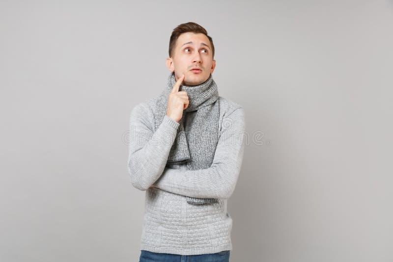 Zadumany młody człowiek w szarym pulowerze, szalik przyglądający w górę, stawiająca ręka podpiera w górę podbródka na popielatym  obraz royalty free