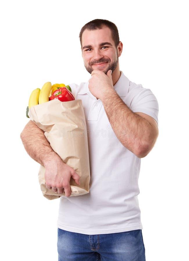 Zadumany mężczyzna trzyma papierową torbę warzywa pełno obrazy royalty free