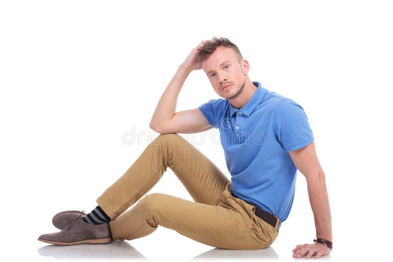 Zadumany młodego człowieka obsiadanie na podłoga fotografia royalty free