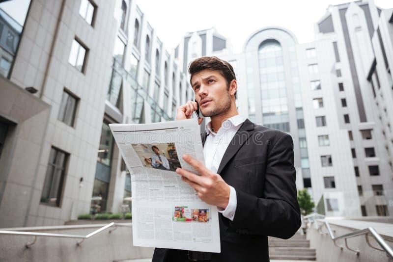 Zadumany młody biznesmen opowiada na telefonie komórkowym i czytelniczej gazecie zdjęcia stock
