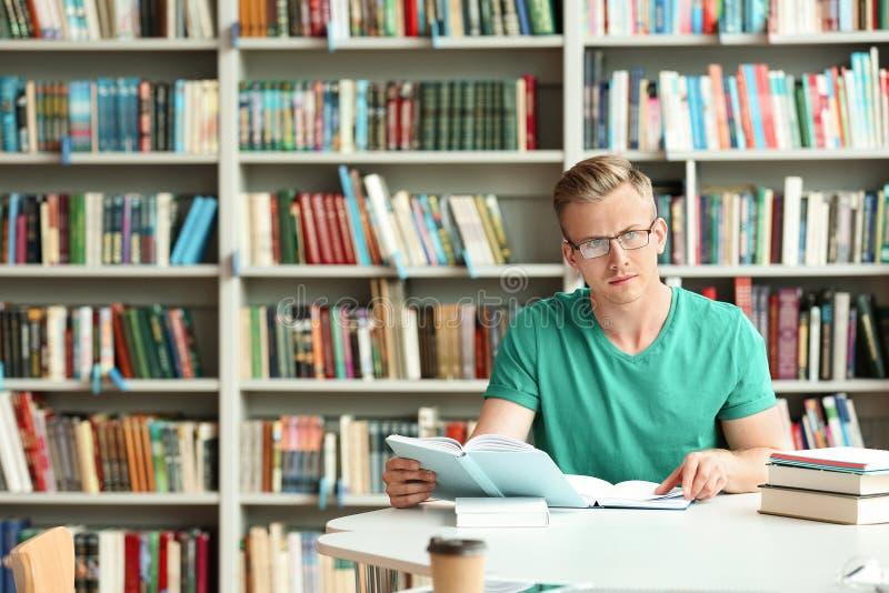 Zadumany młody człowiek z książkami przy stołem w bibliotece zdjęcia stock