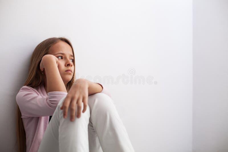 Zadumany młody nastolatek dziewczyny obsiadanie ścianą na podłoga zdjęcia royalty free