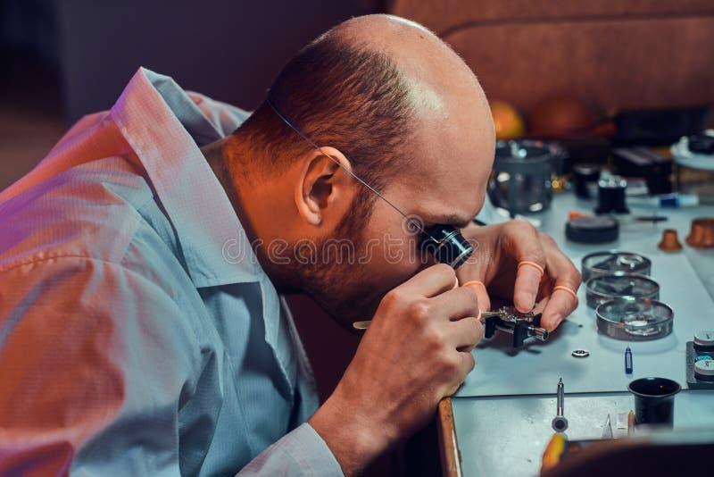 Zadumany mistrz pracuje na klienta zegarku przy jego warsztatem zdjęcia stock