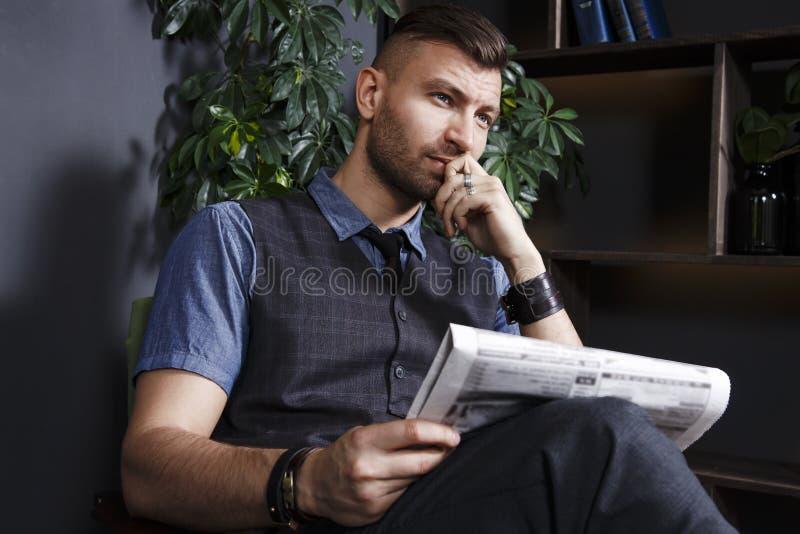 Zadumany modny ufny młody przystojny mężczyzna w krześle z gazetą w luksusowym wnętrzu zdjęcie royalty free