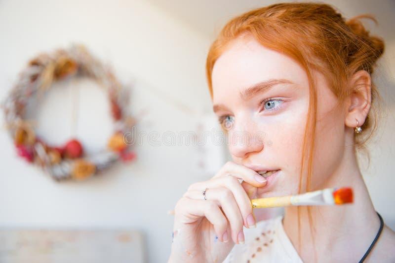 Zadumany piękny młody żeński mienia paintbrush, główkowanie i zdjęcia stock