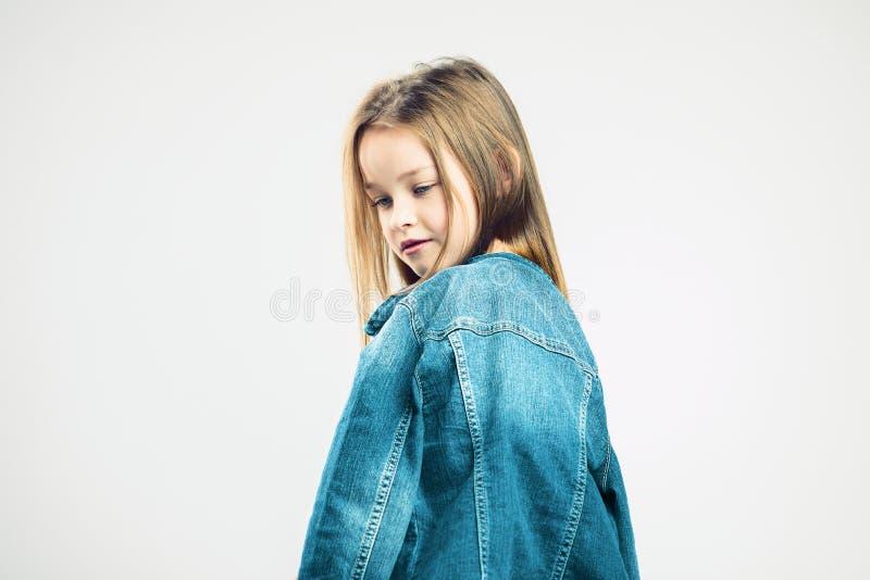 Zadumany portret dziecko mała dziewczynka w drelichowej kurtce pozuje w studiu moda dzieci Szary t?o Portret obrazy stock