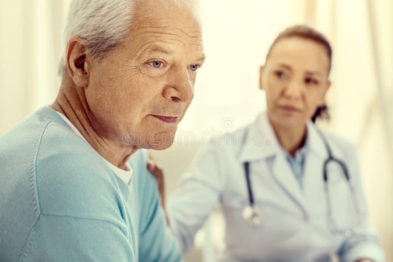 Zadumany przechodzić na emeryturę mężczyzna przyglądający spęczenie podczas medycznej konsultaci fotografia royalty free