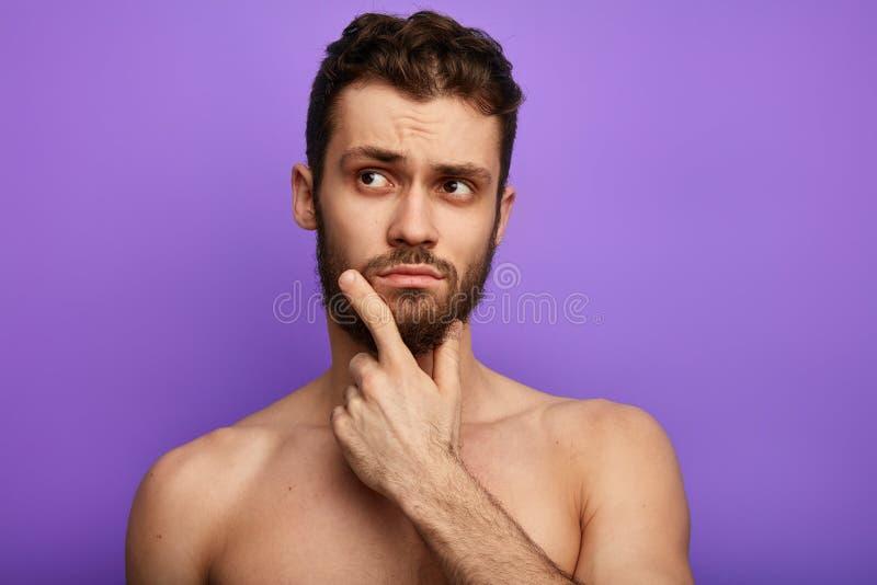 Zadumany rozważny bez koszuli facet patrzeje na boku zdjęcie royalty free