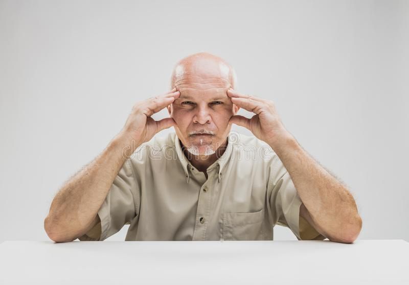 Zadumany starszy mężczyzna z skupiającym się wyrażeniem zdjęcia royalty free