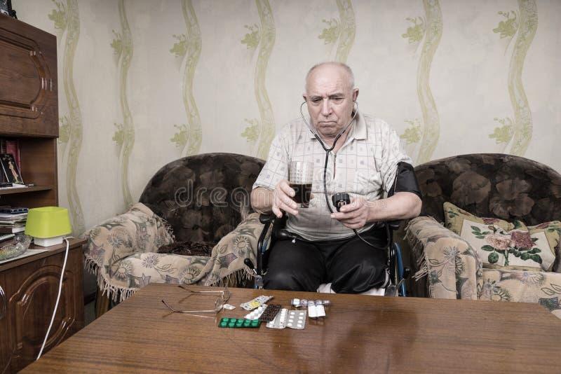 Zadumany stary człowiek Patrzeje Prosto przy jego medycynami fotografia royalty free