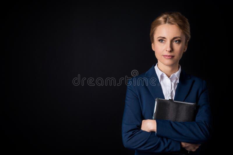 Zadumany w średnim wieku bizneswoman trzyma cyfrową pastylkę i patrzeje daleko od zdjęcie stock