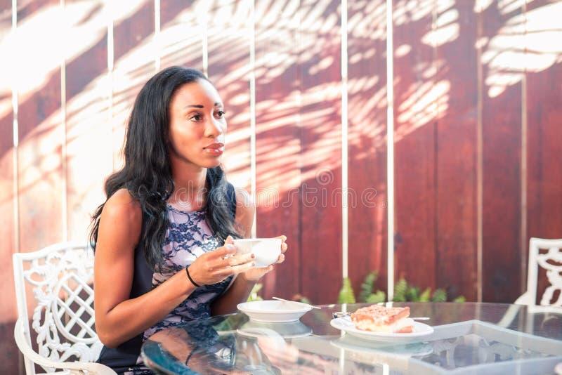 Zadumany zmrok skinned kobiety ma śniadanie przy stołem na zdjęcie stock