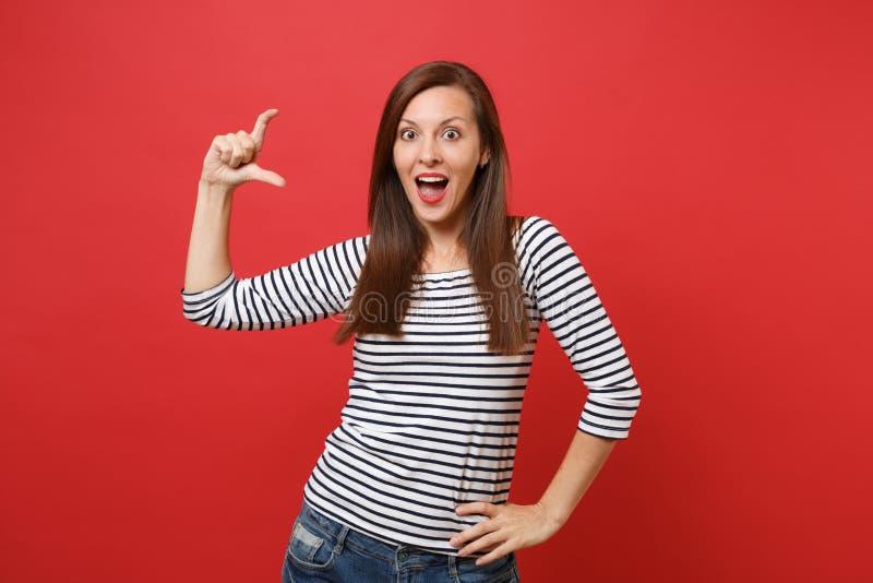 Zadziwiająca młoda kobieta gestykuluje demonstrujący rozmiar z kopii przestrzenią patrzeje zaskakujący odosobnionego dalej, utrzy fotografia stock