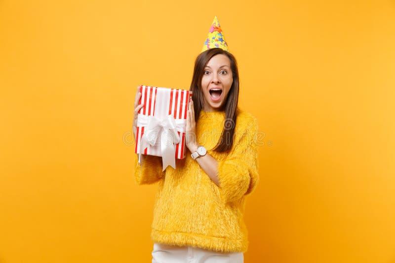 Zadziwiająca młoda kobieta w przyjęcie urodzinowe chwyta czerwieni kapeluszowym pudełku z prezent teraźniejszości odświętnością c obrazy royalty free