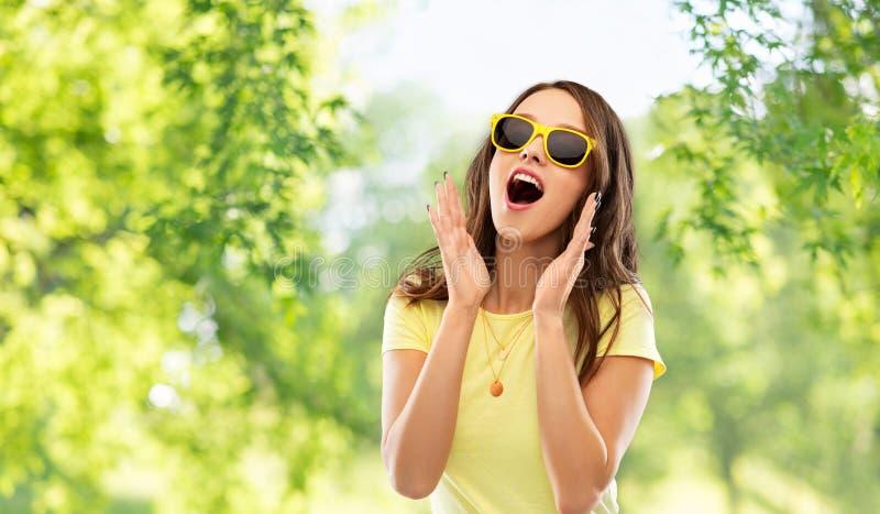 Zadziwiająca nastoletnia dziewczyna w żółtych okularach przeciwsłonecznych zdjęcia royalty free