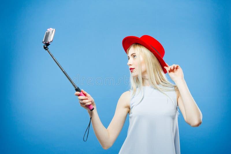Zadziwiająca blondynka ono Fotografuje z Zmysłowymi wargami i Red Hat Uśmiechnięta dziewczyna Używa Selfie kij Brać fotografię da zdjęcie stock