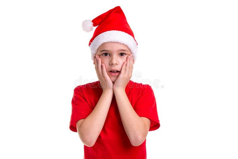 Zadziwiająca chłopiec, Santa kapelusz na jego głowie Pojęcie: boże narodzenia lub Szczęśliwy nowego roku wakacje obraz royalty free