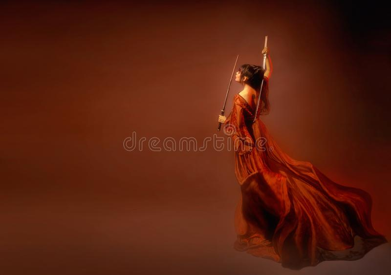 Zadziwiająca ciemnowłosa Japońska samuraj kobieta, młoda dziewczyna w światło długiej czerwonej trzepotliwej sukni z otwartym i t obrazy royalty free