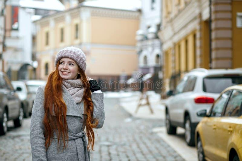 Zadziwiająca czerwieni głowy dziewczyna jest ubranym zimy nakrętkę pwalking przy th żakiet i fotografia stock