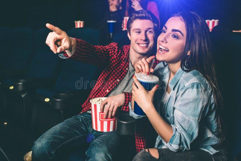 Zadziwiająca i rozochocona dziewczyna jest roześmiana Pije kolę od błękitnej filiżanki Facet chce chwytać jej wskazywać i uwagę obraz stock