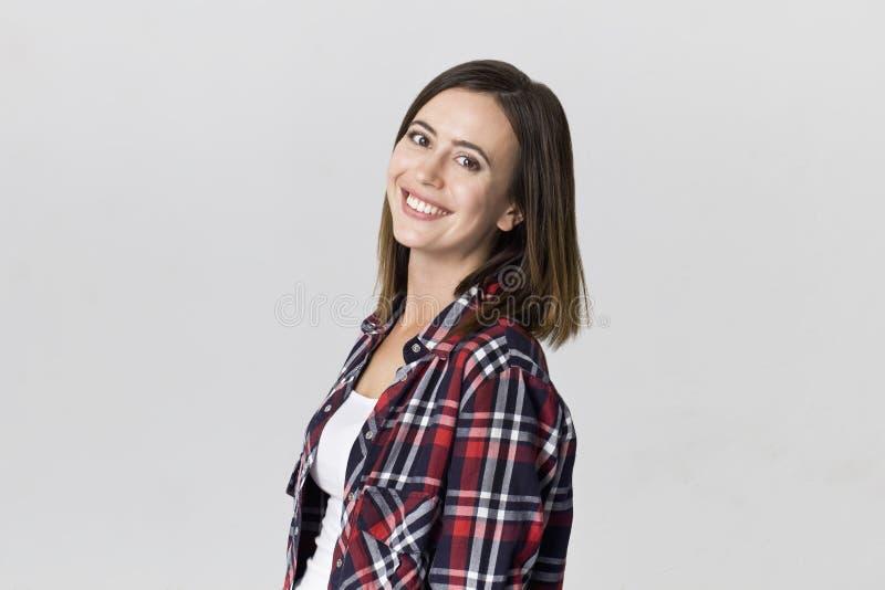 Zadziwiająca i rozochocona uśmiechnięta brunetki kobieta w pięknym w kratkę koszulowym studio strzale na bielu, zdjęcie royalty free