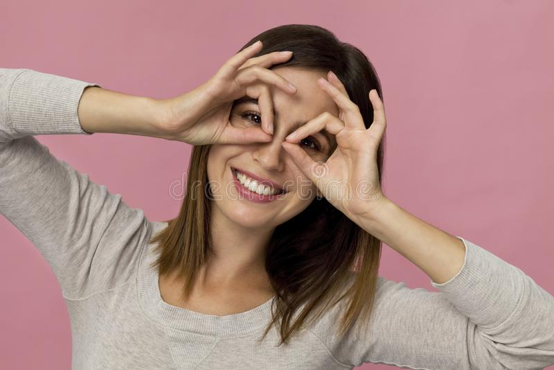 Zadziwiająca i rozochocona uśmiechnięta brunetki kobieta w pięknym smokingowym studio strzale, różowy tło fotografia royalty free