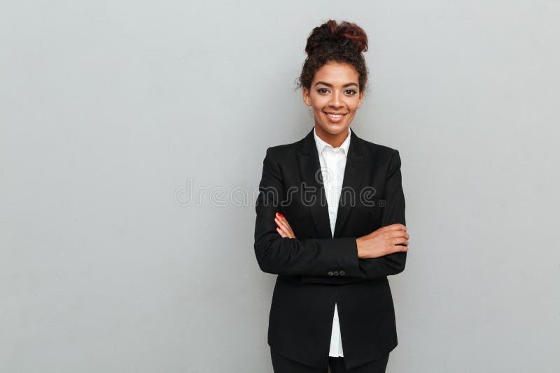 Zadziwiająca młoda afrykańska biznesowa kobieta stoi nad popielatą ścianą fotografia royalty free