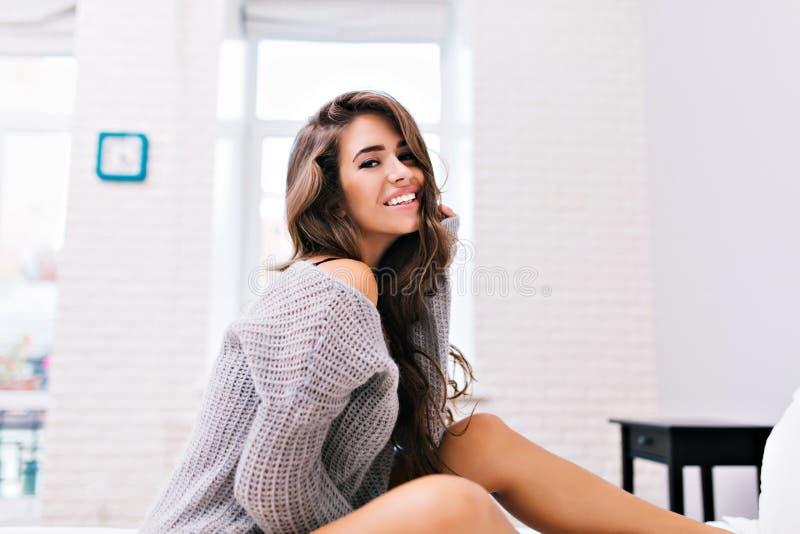Zadziwiająca radosna ładna dziewczyna z długiej brunetki włosiany ono uśmiecha się na łóżku w nowożytnym białym mieszkaniu Modni  zdjęcia stock