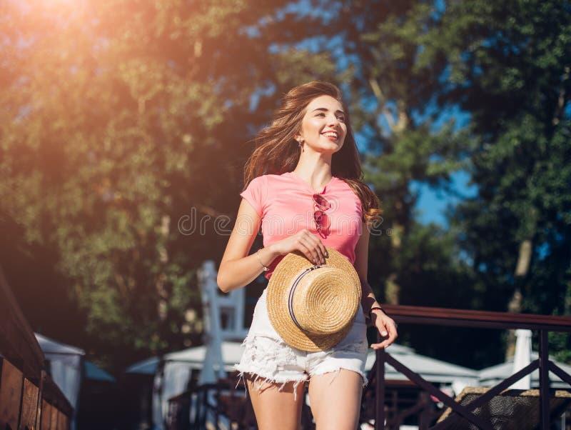Zadziwiająca radosna ładna dziewczyna z długim brunetka włosy mieć zabawę na plaży, tanu i ono uśmiecha się, być na wakacjach nas obrazy stock