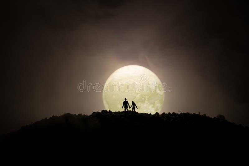 Zadziwiająca scena miłosna Sylwetki młoda romantyczna pary pozycja pod księżyc światłem obraz royalty free