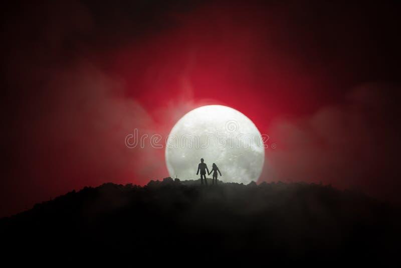 Zadziwiająca scena miłosna Sylwetki młoda romantyczna pary pozycja pod księżyc światłem zdjęcia royalty free