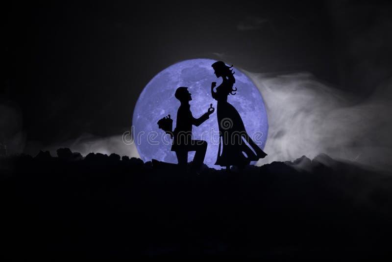 Zadziwiająca scena miłosna Sylwetki robi propozyci kobieta przeciw dużej księżyc przy tłem mężczyzna lub sylwetki para zdjęcie stock