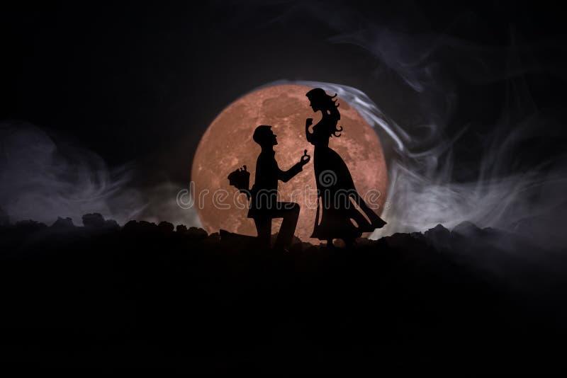 Zadziwiająca scena miłosna Sylwetki robi propozyci kobieta przeciw dużej księżyc przy tłem mężczyzna lub sylwetki para zdjęcie royalty free