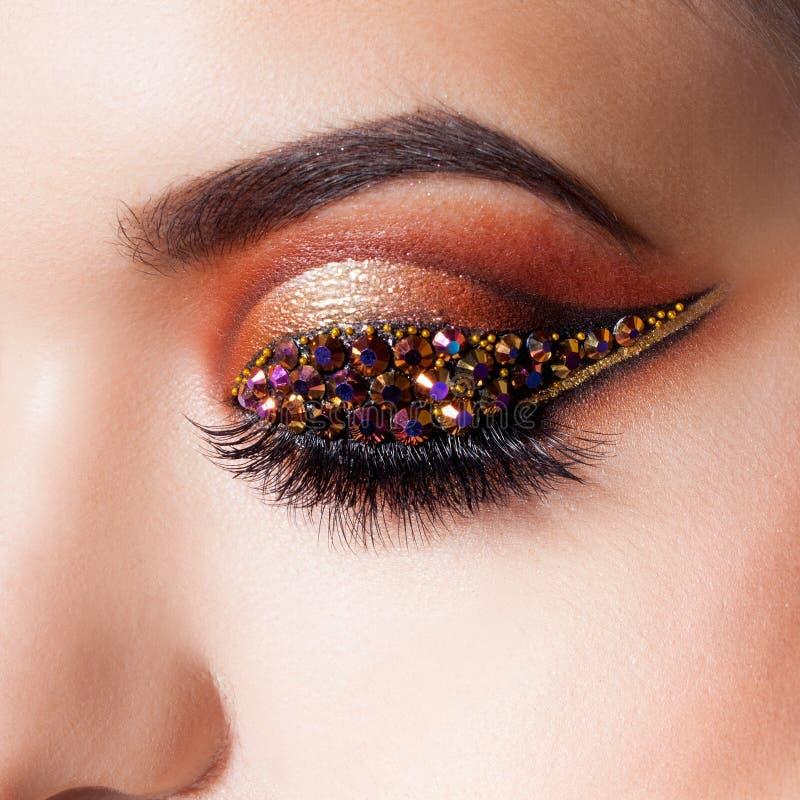 Zadziwiający Jaskrawy oka makeup z strzałą z rhinestones Brown i złociści brzmienia, barwiony eyeshadow obraz stock