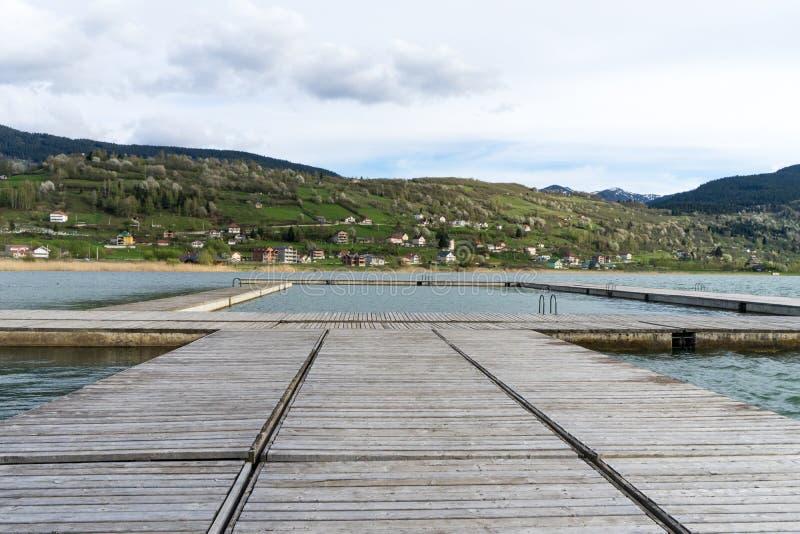 zadziwiający widok drewniany molo w jeziorze z halnym scenerii tłem Plav jezioro Montenegro fotografia royalty free