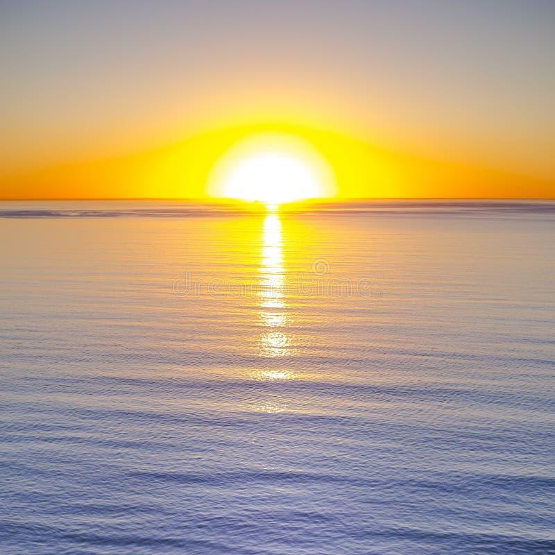 Zadziwiający zmierzch z pomarańczowym niebem i spokój wodą zdjęcia stock