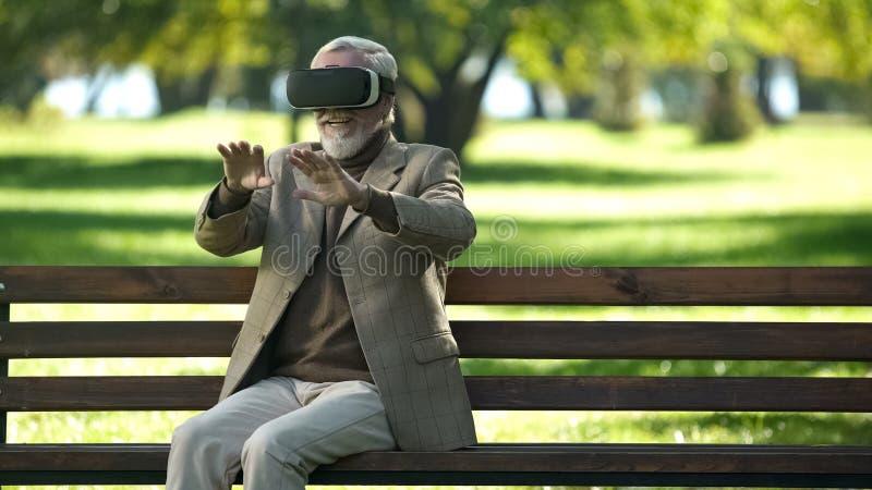 Zadziwiaj?cy starszy m??czy?ni u?ywa VR s?uchawki outdoors, nowo?ytny technologii do?wiadczenie obrazy royalty free
