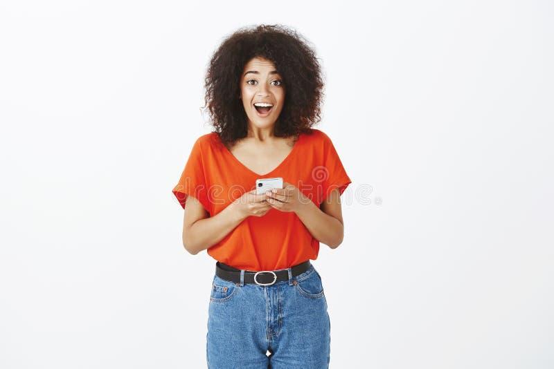 Zadziwiam czarować joyfully, czuły z włosami żeński coworker w modnym stroju mienia smartphone i ono uśmiecha się fotografia stock