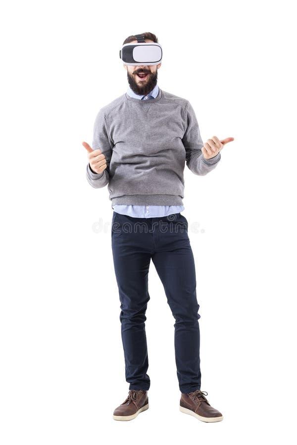Zadziwiam excited szczęśliwego młodego dorosłego mężczyzna jest ubranym rzeczywistość wirtualna szkła z aprobata gestem fotografia stock