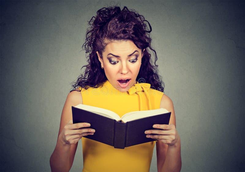 Zadziwiam szokował kobiety czyta książkę zdjęcia stock