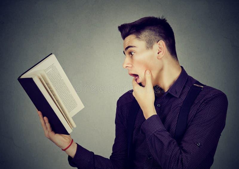 Zadziwiam szokował mężczyzna czyta książkę zdjęcie royalty free
