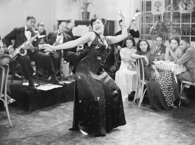 Zaftig kvinna som framme utför en dans av en grupp människor i en restaurang (alla visade personer inte är längre uppehälle och i royaltyfri fotografi