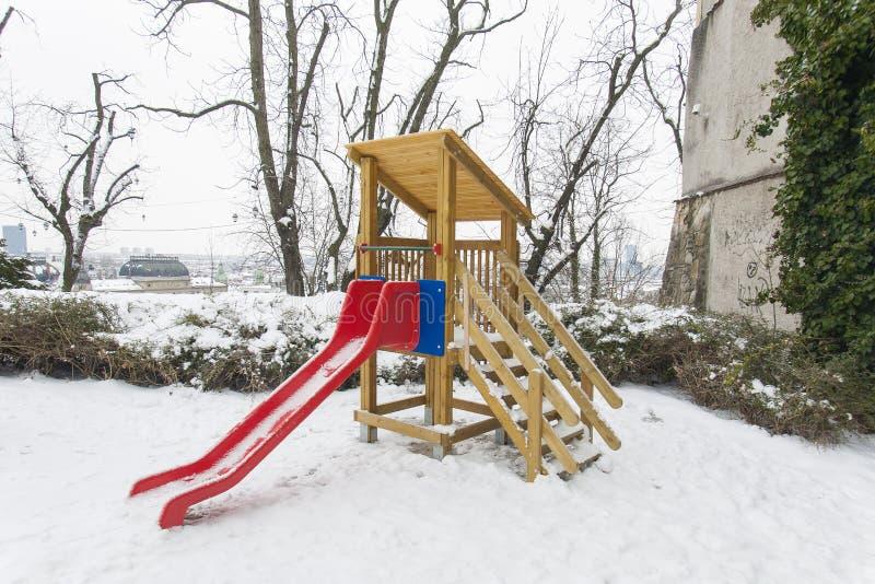 ZAGREB CHORWACJA, LUTY 2018 A czerwony obruszenie w dziecka boisku zakrywającym z białym śniegiem, - fotografia stock