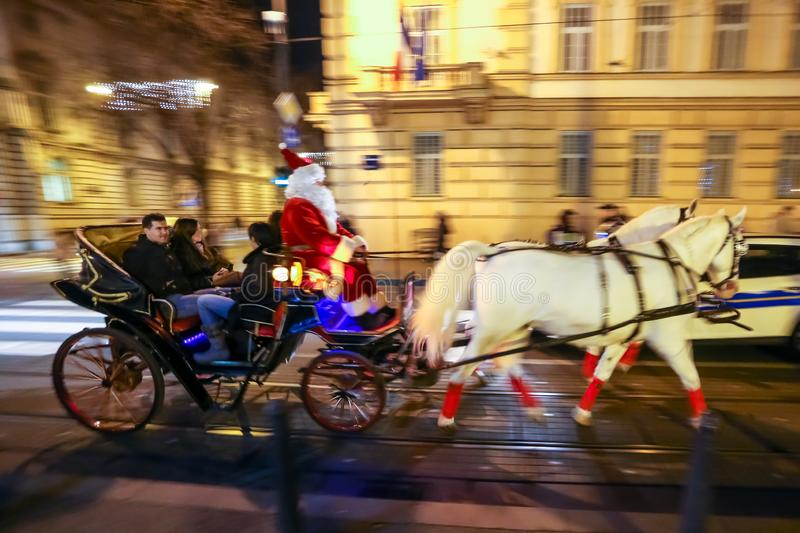 Advent Zagreb 2018. Zagreb, Croatia - December 13, 2018: People driving in a carriage with horses and a man dressed in a Santa Claus suit as a driver on the royalty free stock photo