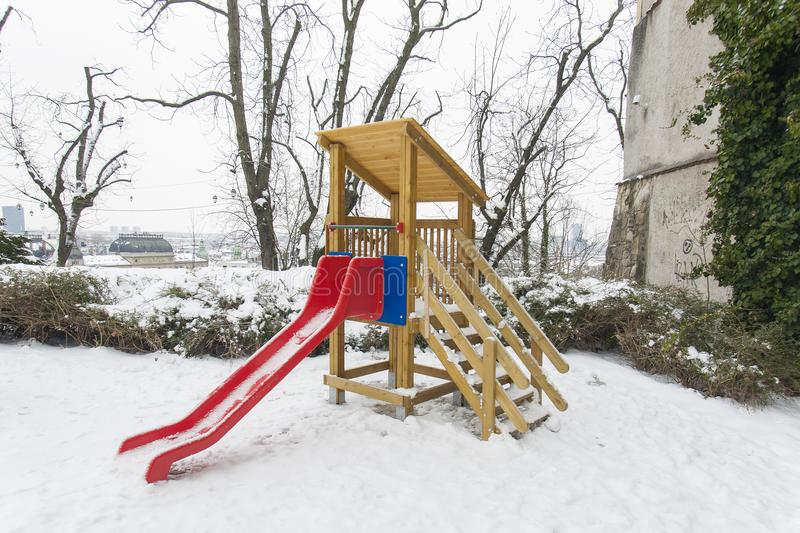 ZAGREB, CROATIA - FEBRUARY 2018 A red slide in a children playground covered with white snow stock photography