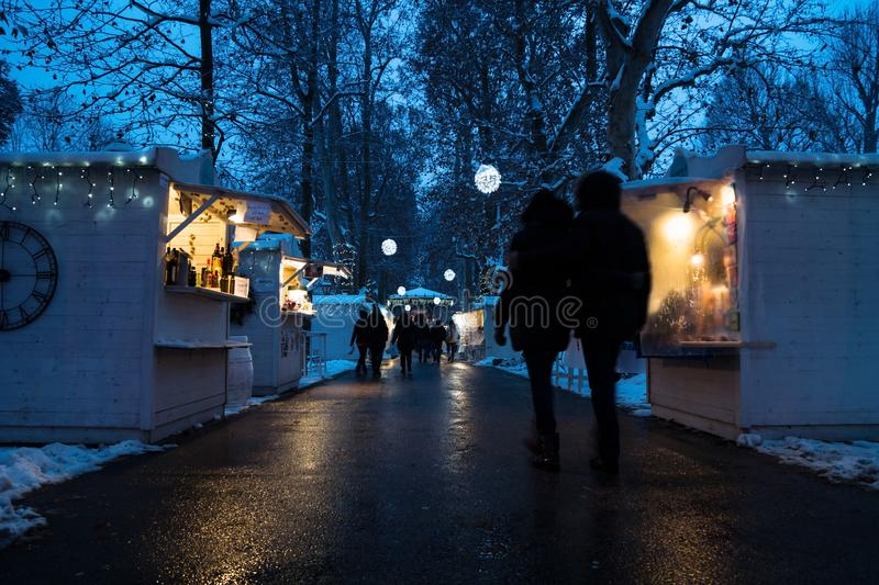 Zagreb, Croatia: January 6 2016: Advent market with foodstalls and lights with vistors in the night with snow in Zrinjevac Park in stock images